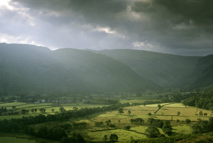Borrowdale, Cumbria,  bathed in stormy sunlight as seen from Lingy Bank with Watendlath Fell on the left