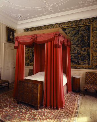 The Spenser Room at Canons Ashby with original valance, tester and headcloth on the bed, and a 17th century Flemish tapestry on the wall