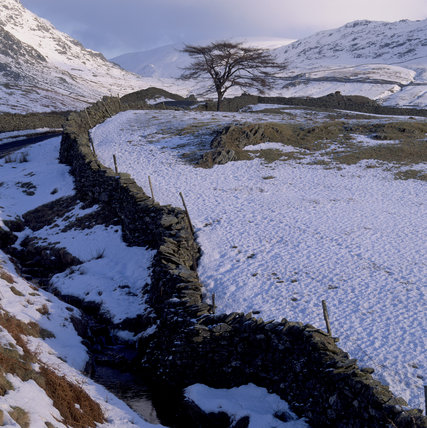 Kirkstone Pass, looking up towards the pass from the south, a drystone wall cuts across the snow covered landscape