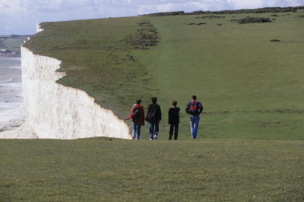 View of a group of walkers strolling along the cliff top, on the South Downs Way, above Seven Sisters