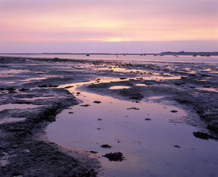 A view of Blakeney Point at low tide looking out across some sandy flats towards an area where various boats are anchored