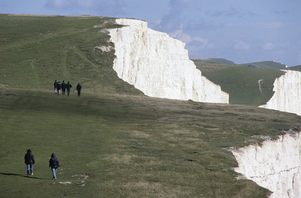View of groups of ramblers walking along the cliff top on the South Downs Way, above Seven Sisters, enjoying the spectacular coastal scenery