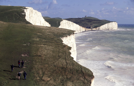 View of ramblers walking along the cliff top on the South Downs Way, above Seven Sisters, with the spectacular white cliffs and sea below.