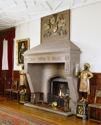 The Inner Hall fireplace at Dunster Castle, showing chimney piece installed by Salvin in C19th, overmantel with Luttrell coat of arms, human figures either side and ceiling detail
