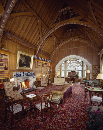 General view of Library at Tyntesfield through carved stone archway to stone gothic window, with stone & marble fireplace in foreground & collar beamed roof above