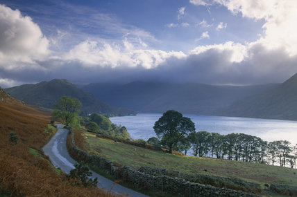 A landscape photo of Crummock Water, near Buttermere with the light filtering down through clouds towards the right of the scene