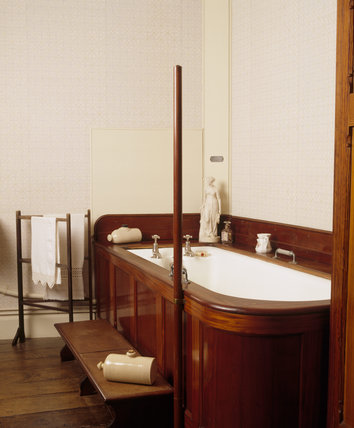 The bathroom at Dunster Castle showing the mahogany panelling enclosing the bath, access steps, stone hot water bottles, clothes horse and small porcelain figure on the bath surround