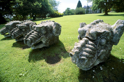 A view of four large griffin heads displayed on the lawn at Wallington