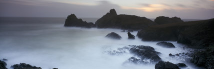 Waves breaking on jagged rocks in Kynance Cove, creating a mist