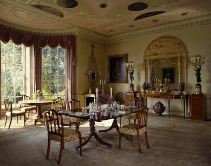 The Dining Room at Hinton Ampner showing the elaborate ceiling decoration and the large golden mirror