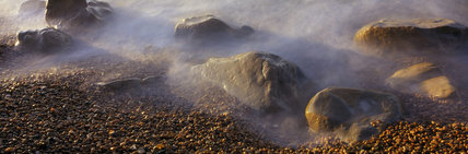 Mist from the sea breaking over boulders on East Ebb Beach