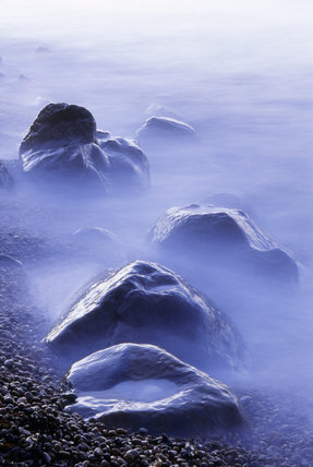 Glistening boulders catching the twilight amidst the foaming sea