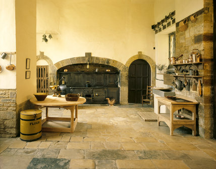 Canons Ashby - The Kitchen with Victorian cast iron range and cooking utensils and stone flagged floor