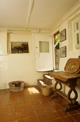 View to the open back-door in the Kitchen at Monk's House, with a red tiled floor