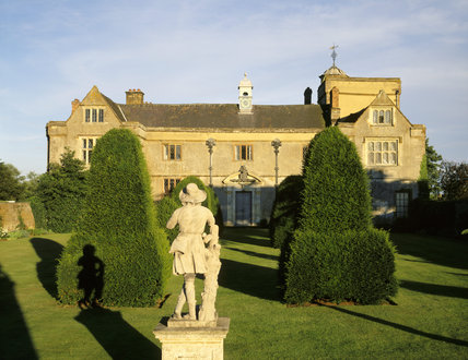 A view of the west front of Canons Ashby from the Green Court showing a lead statue of a young shepherd with his dog in the foreground