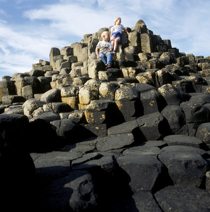 A boy ang girl sit on some stacked rocks in Giant's Causeway