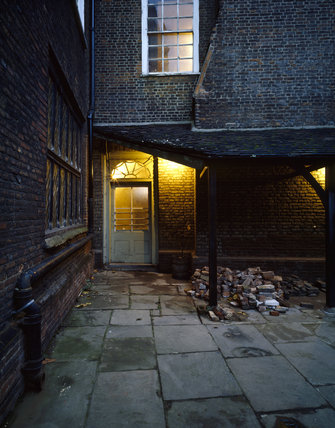 C16th courtyard at Sutton House, light shining in the porch which dates from 1904
