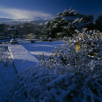 Looking out from a wintery terrace at Bodnant Garden, over the snow covered countryside and away to the distant hill