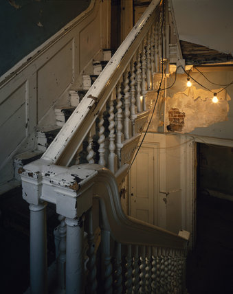 East staircase C18th at Sutton House in need of repair, lit with bare light bulbs