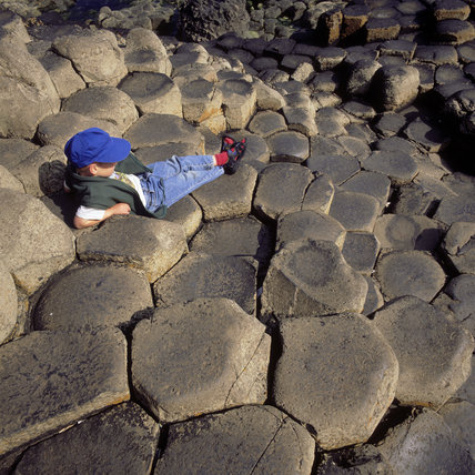 A little boy takes a rest on the rocks in Giant's Causeway