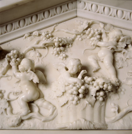 A detailed close up of part of the chimney-piece in the Saloon, showing cherub like figures eating grapes from the vines