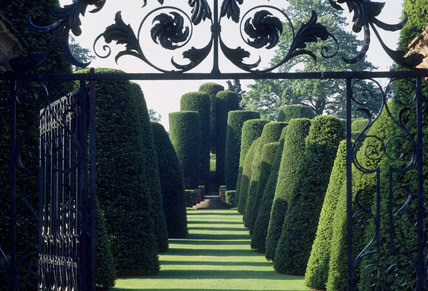 C18th gate leading to Avenue of Giant Yews in the gardens at Packwood House in the Summer