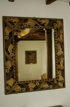 A view showing the mirror with a canvas work frame in the Hall at Monk's House