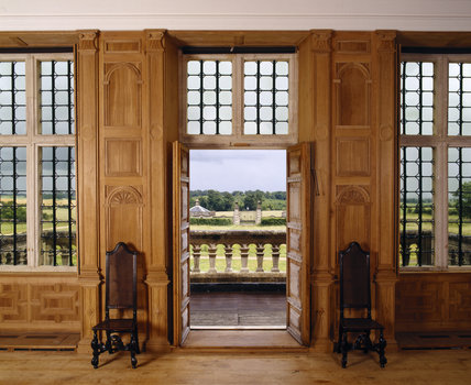 View of the Great Room showing open doors, chairs flanking doorway, windows, balcony and view into the park