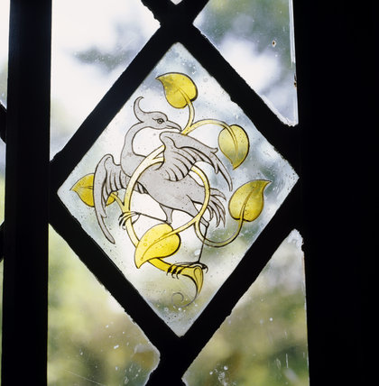 Stained glass panel of a bird in a window of the Great Hall at Stoneacre, a medieval Weladen house in Kent