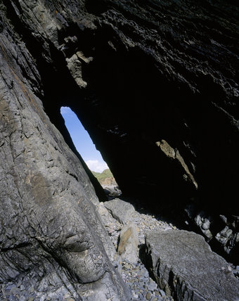 A tall narrow slot eroded through the rock on the beach, at Marloes Sands