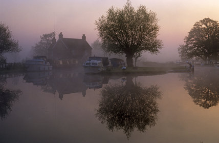 A peaceful mist shrouded scene at Papercourt Lock with the trees and cottage reflected in the still water