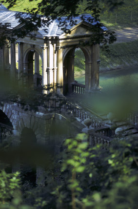 The Palladian Bridge, Prior Park, seen through trees from the slopes of the Wilderness