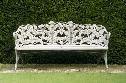 A Victorian cast iron seat with a fern motif, in the garden at Anglesey Abbey