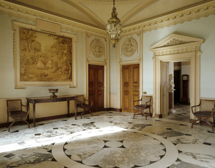 The Marble Hall showing the black, white and grey marble floor, the wool tapestry, made about 1901, the veneered Spanish mahogany doors and ornate plaster roundels over the doors