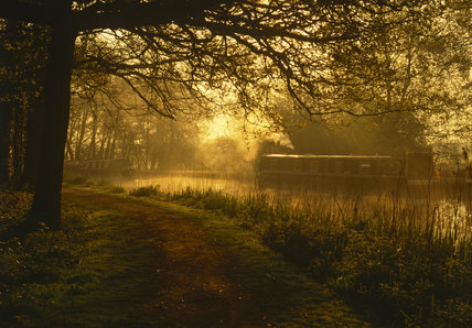 Dawn light illuminates a traditional narrowboat, with a wisp of smoke, moored upstream of Papercourt Lock
