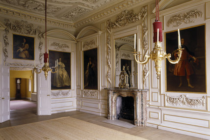 A view of the Saloon showing the full length portraits, the fireplace and the elaborate wall carvings by Edward Pierce of 1678