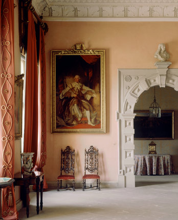 From the Great Hall through the stone arch to theEntrance Passage Reynold's portrait of George III hangs beside the coral coloured curtains above two carved high backed chairs