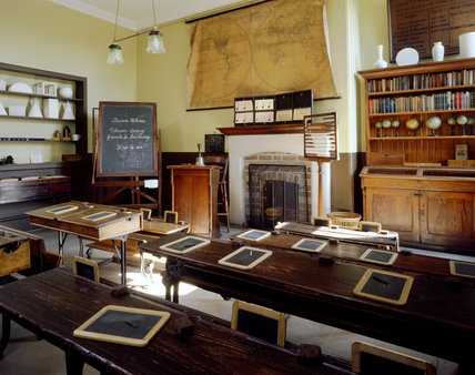 A view of the School Room with a blackboard in the corner writing slates set out on desks, a counting frame and shelves holding specimens of geometric shapes