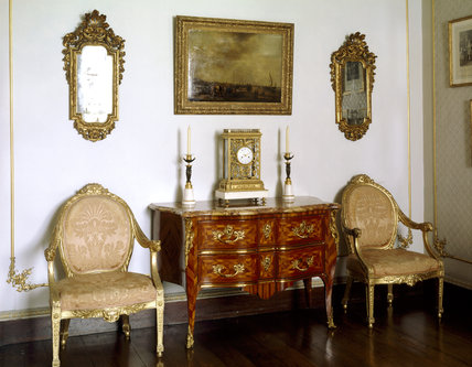 Close-up of furniture from the Digby Collection in the Boudoir including an early Louis XV Commode, French clock by Mignolet pair of gilt Venetian mirrors and a van Goyen landscape
