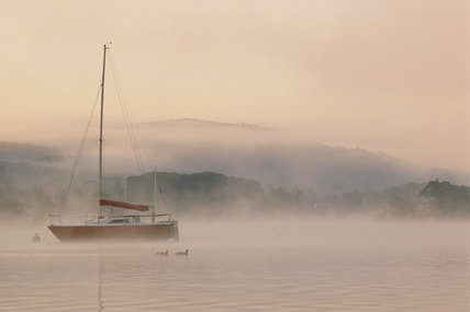 Misty view of boat on Lake Windermere at dawn from Cockshott Point, Cumbria