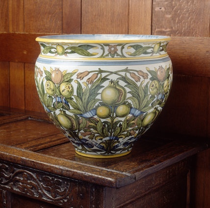 Vase decorated with pomegranates on the chest in the porch