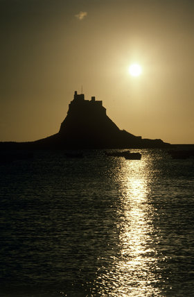 Sunset over Lindisfarne Castle, with boats in the sea