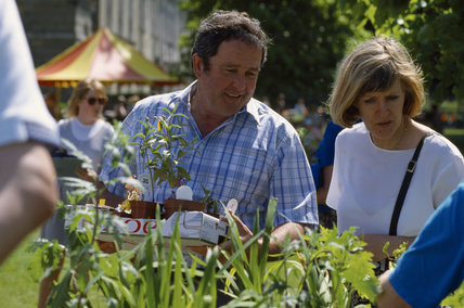 A middle aged man and woman looking at some plants on a stool at a National Trust Spring Fair held at Petworth House