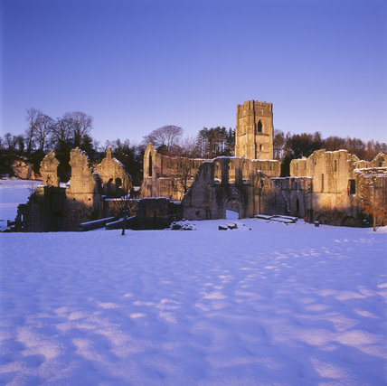 The Abbey standing starkly in the snow, lit by the weak winter sunshine