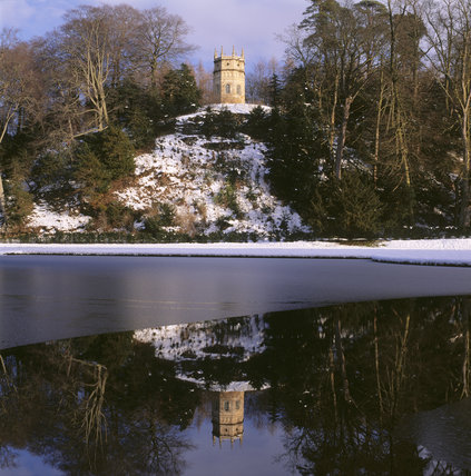 The Octagon Tower in the snow above Small Half Moon Pond, and reflected in the still, half frozen water