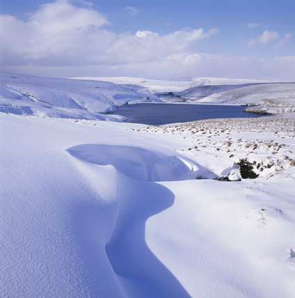 Looking north over the snow covered Wessenden Head, with a reservoir in the middle distance