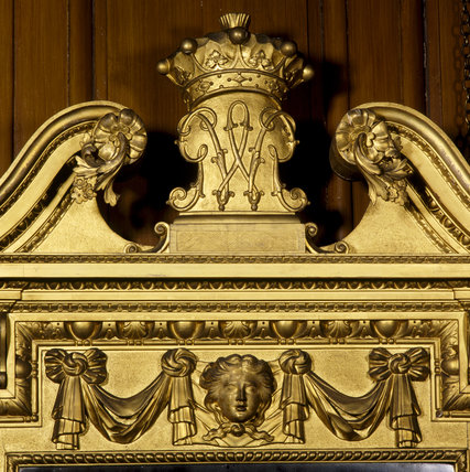 Detail of the pediment of the gilt mirror in the Great Hall at Dunham Massey, showing the crowned monogram of the 2nd Earl of Warrington