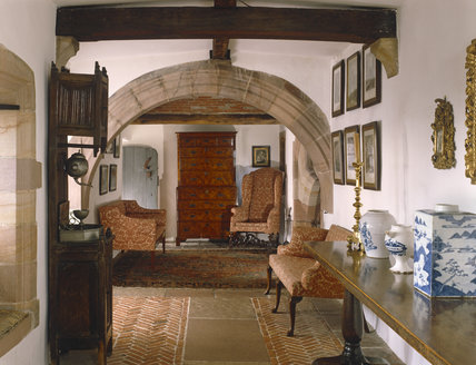 A view of the Long Gallery, showing the rounded arch, wooden cross beam, C17th Flemish walnut refectory table with a collection of blue Delft jars opposite a C16th Dutch aumbry
