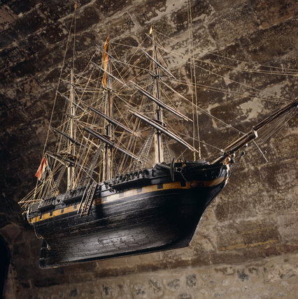 A view of the Ship Room, showing a model, hanging from the centre of the ceiling of an early C19th three-masted merchantman (Henrietta of Amsterdam, 1840), in full rig