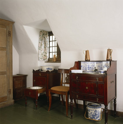 A view of the North East Bedroom showing a mahogany washstand and a chair